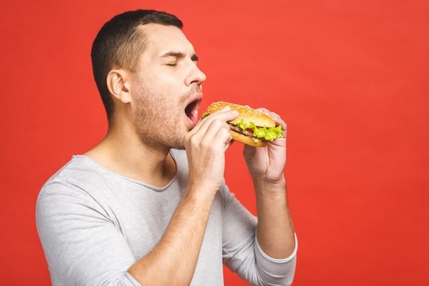 Jovem segurando um pedaço de hambúrguer.