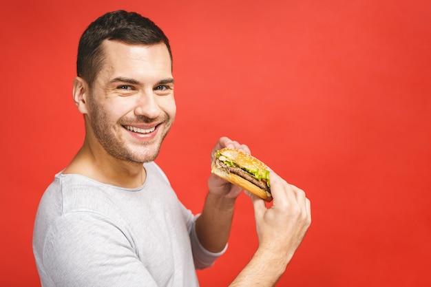 Jovem segurando um pedaço de hambúrguer