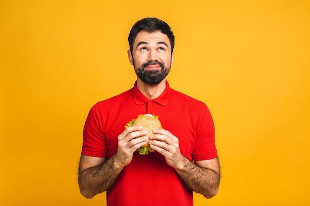 Jovem segurando um pedaço de sanduíche. o aluno come comida rápida. hambúrguer não é alimento útil.