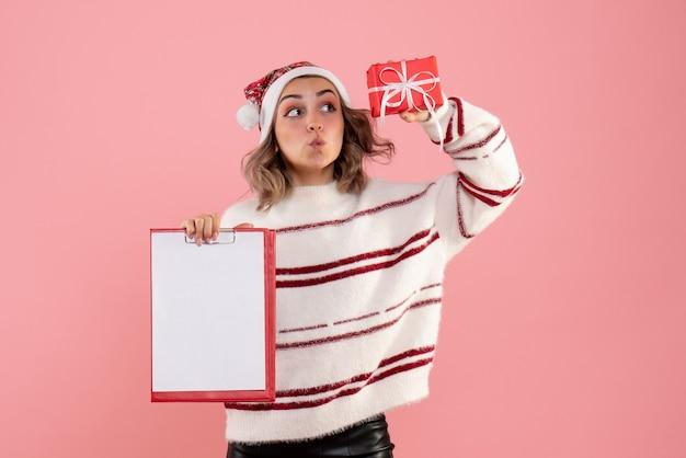 Jovem segurando um pequeno presente de natal e uma nota rosa