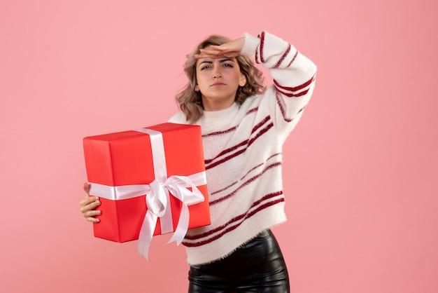 Jovem segurando um presente de natal e olhando no rosa