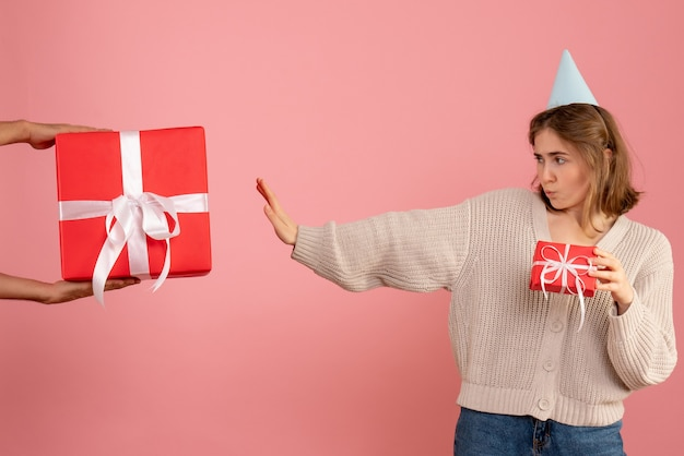 Jovem segurando um presente de natal e rejeitando o presente do macho na rosa