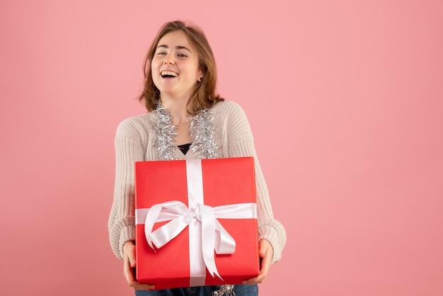 Jovem segurando um presente de natal rosa
