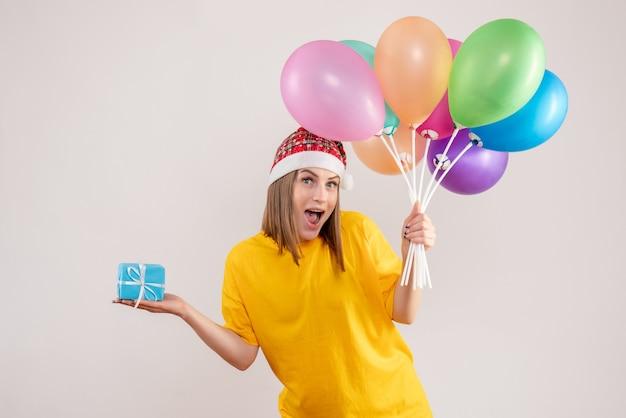 Jovem segurando um presentinho e balões coloridos em branco