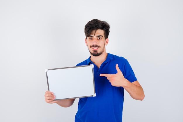 Jovem segurando um quadro branco e apontando para ele com uma camiseta azul e parecendo feliz