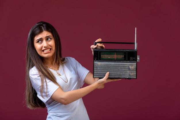 Jovem, segurando um rádio vintage na mão e perturbada pelo volume.