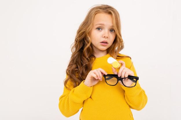 Jovem, segurando um recipiente para lentes e óculos na mão