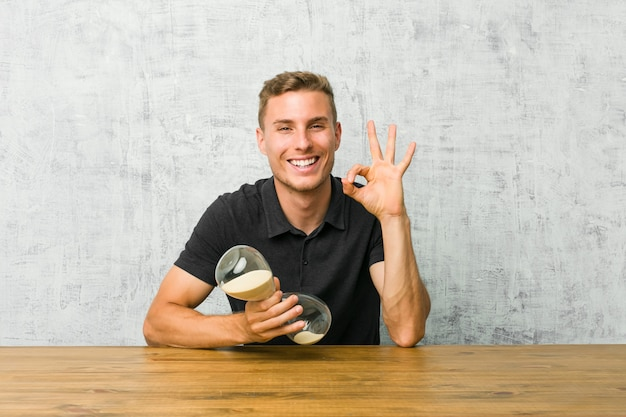 Jovem, segurando um relógio de areia em uma mesa pisca um olho e mantém um gesto bem com a mão.