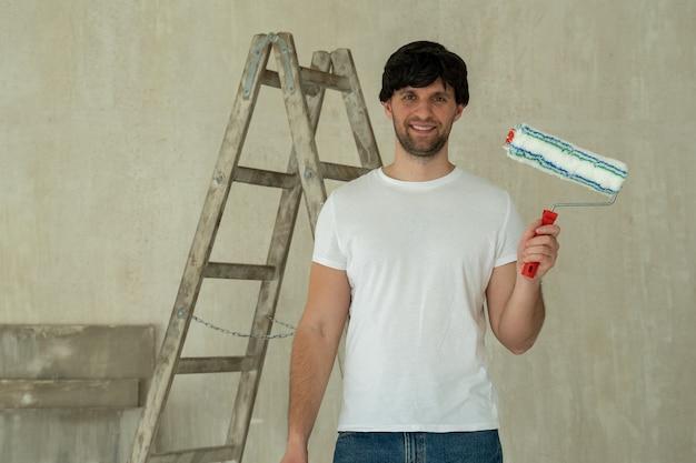 Jovem segurando um rolo contra uma escada. pintor de casas faz reparos em casa