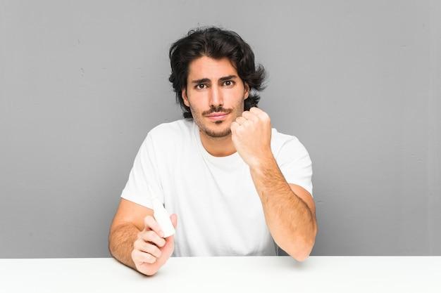 Jovem, segurando um spray nasal mostrando o punho com expressão facial agressiva.