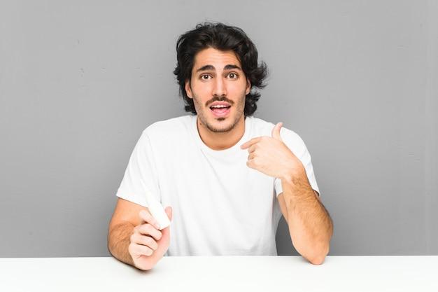 Jovem, segurando um spray nasal surpreendeu apontando para si mesmo, sorrindo amplamente.