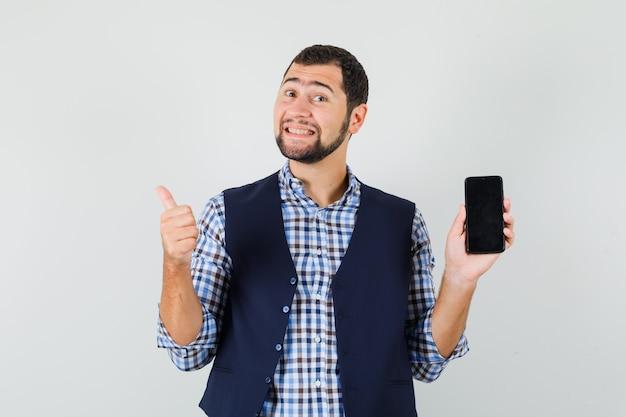 Jovem segurando um telefone celular, mostrando o polegar na camisa