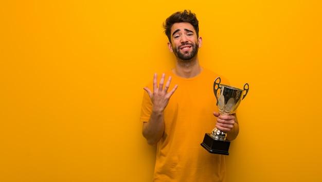 Jovem, segurando um troféu muito assustado e com medo