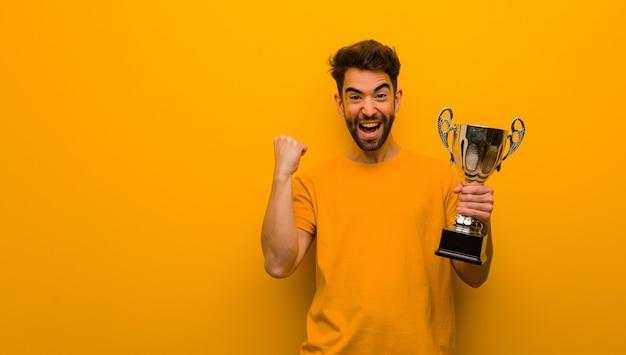 Jovem, segurando um troféu surpreso e chocado