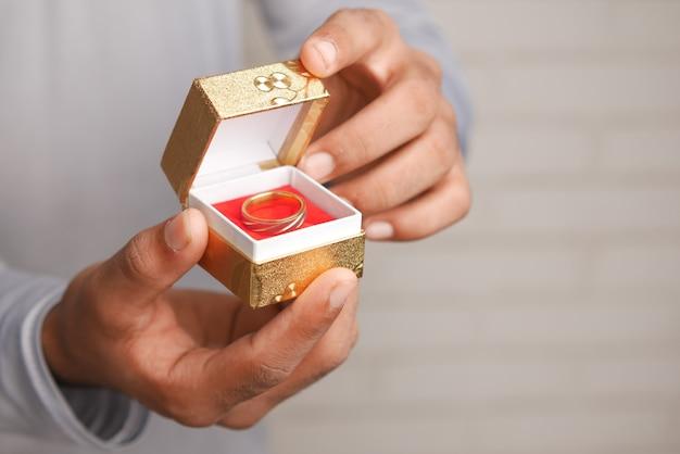 Jovem segurando uma aliança de casamento em uma caixa