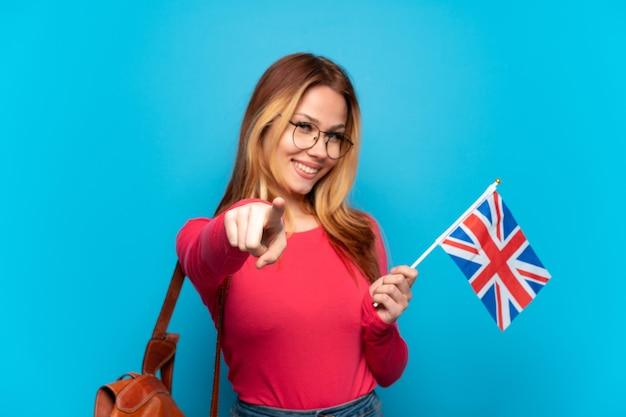 Jovem segurando uma bandeira do reino unido sobre um fundo azul isolado apontando para a frente com uma expressão feliz
