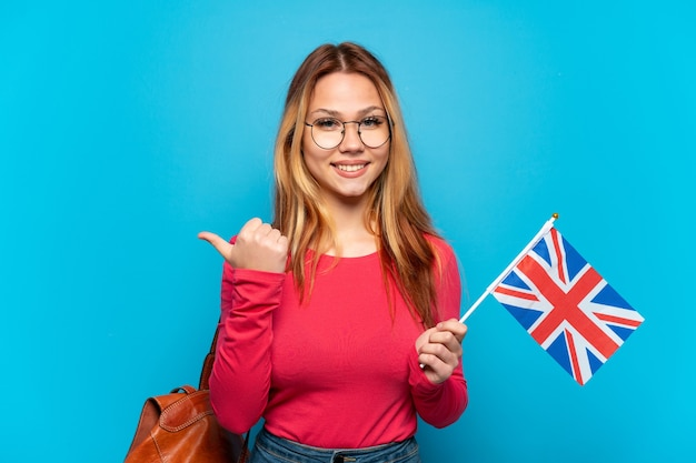 Jovem segurando uma bandeira do reino unido sobre um fundo azul isolado apontando para o lado para apresentar um produto