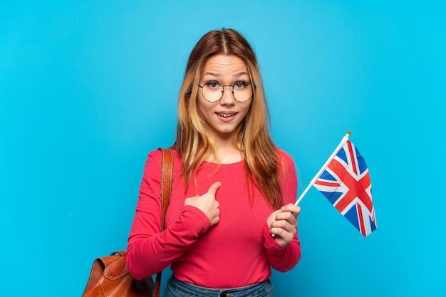 Jovem segurando uma bandeira do reino unido sobre um fundo azul isolado com expressão facial de surpresa