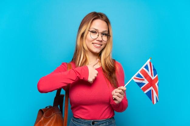 Jovem segurando uma bandeira do reino unido sobre um fundo azul isolado e fazendo um gesto de polegar para cima