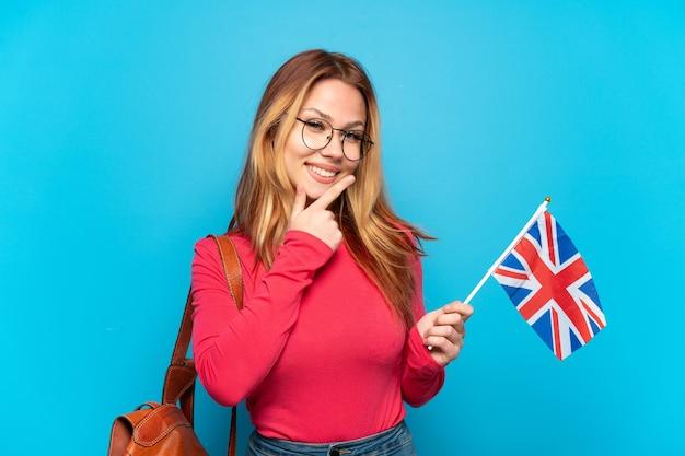 Jovem segurando uma bandeira do reino unido sobre um fundo azul isolado, feliz e sorridente