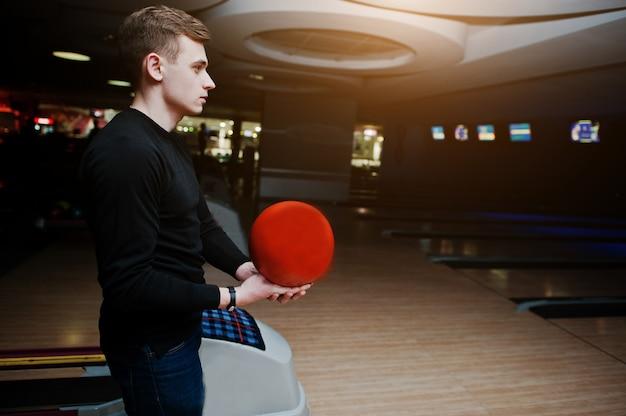Jovem, segurando uma bola de boliche em pé contra pistas de boliche com luz ultravioleta.