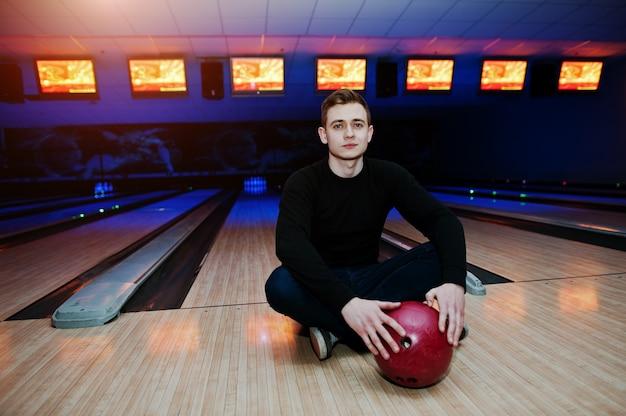 Jovem, segurando uma bola de boliche, sentado contra pistas de boliche com luz ultravioleta.