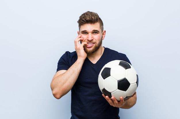 Jovem, segurando uma bola de futebol, roer unhas, nervoso e muito ansioso