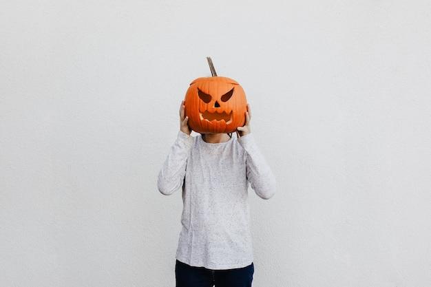 Jovem segurando uma cabeça de abóbora esculpida como sua cabeça no fundo da parede branca. humor da temporada de halloween.