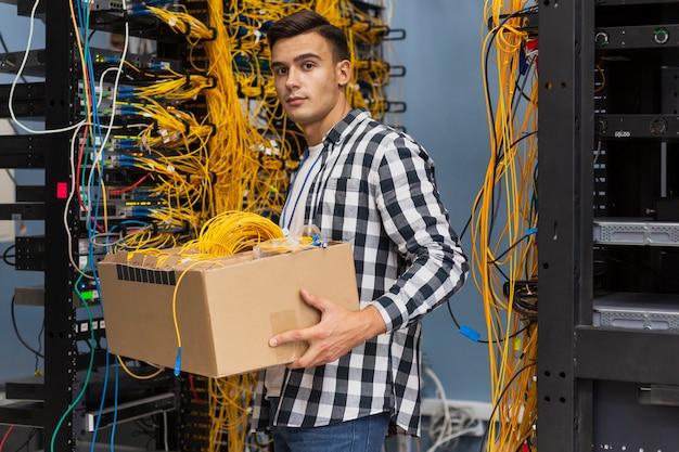 Jovem, segurando uma caixa com fios