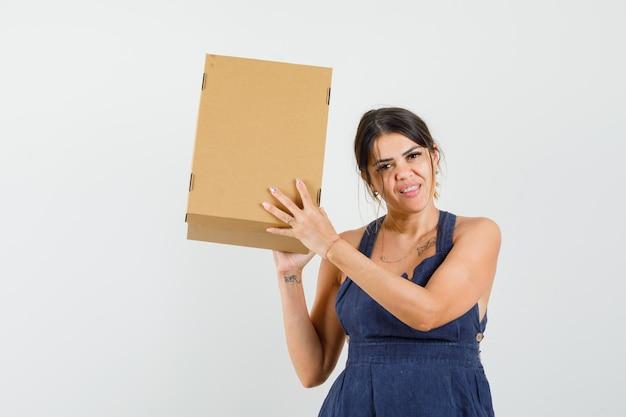 Jovem segurando uma caixa de papelão no vestido e parecendo feliz