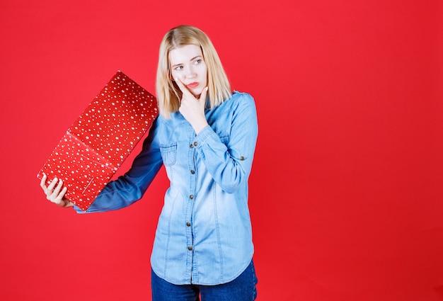 Jovem segurando uma caixa de presente de aniversário e mantendo o dedo no rosto