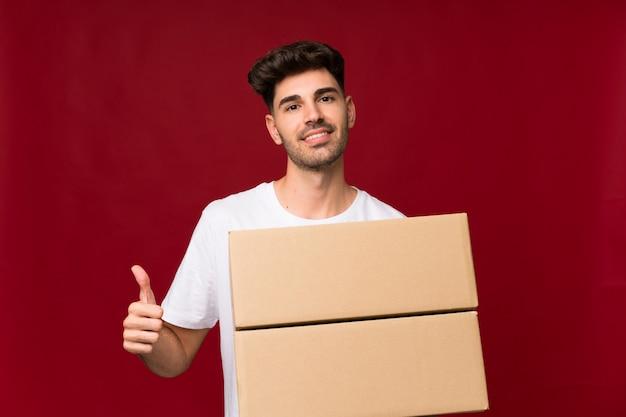 Jovem, segurando uma caixa para movê-lo para outro site com o polegar para cima