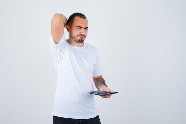 Jovem segurando uma calculadora e colocando a mão atrás da cabeça em uma camiseta branca e calça preta e parecendo pensativo