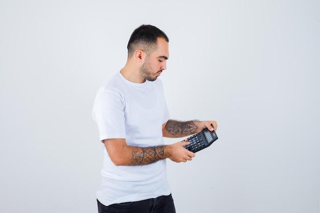 Jovem segurando uma calculadora e fazendo operações nela em uma camiseta branca e calça preta e parecendo sério