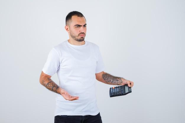Jovem segurando uma calculadora e pensando em algo em uma camiseta branca e calça preta e parecendo pensativo
