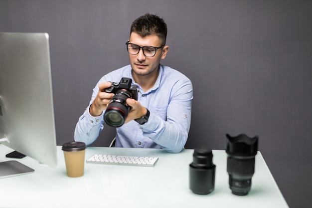 Jovem segurando uma câmera digital e sorrindo enquanto está sentado em seu local de trabalho
