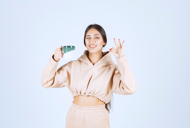 Jovem segurando uma caneca verde e mostrando sua satisfação