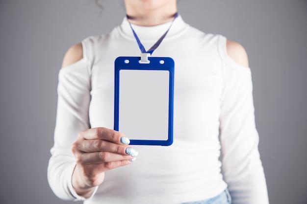 Jovem segurando uma carteira de identidade em uma cena cinza