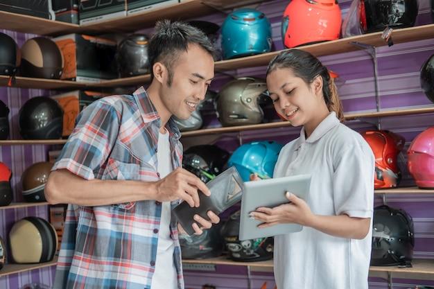 Jovem segurando uma carteira para pagar enquanto é servido por um lojista usando um tablet em uma loja de capacetes