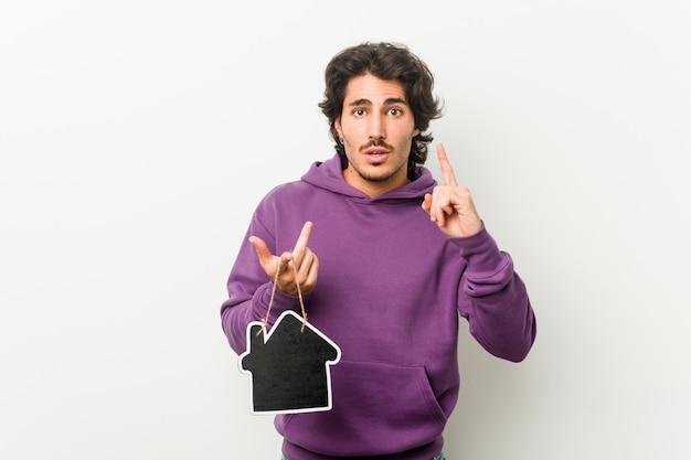 Jovem, segurando uma casa ícone forma tendo uma idéia, conceito de inspiração.