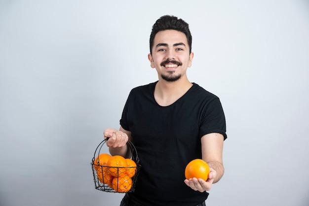 Jovem segurando uma cesta metálica cheia de frutas laranja.