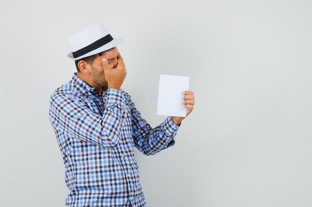 Jovem segurando uma folha de papel em uma camisa xadrez