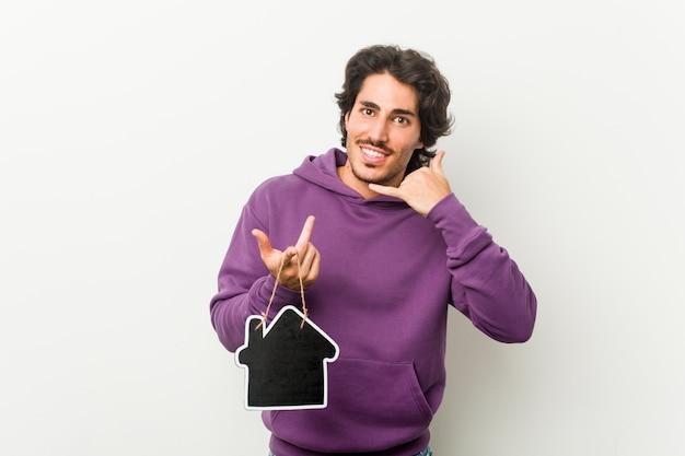 Jovem, segurando uma forma de ícone de casa mostrando um gesto de chamada de telefone móvel com os dedos.
