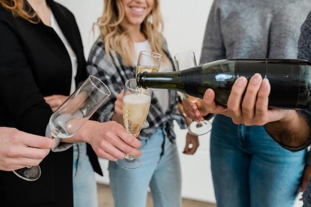 Jovem segurando uma garrafa de champanhe enquanto derrama o refrigerante em uma das taças seguradas por amigos na festa antes de brindar