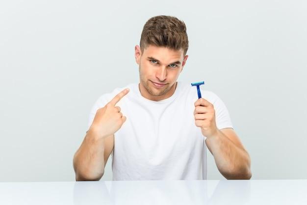 Jovem, segurando uma lâmina de barbear, apontando com o dedo para você, como se estivesse convidando para se aproximar