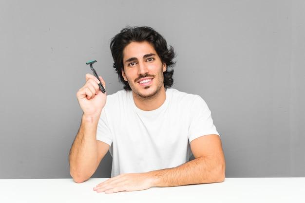 Jovem, segurando uma lâmina de barbear feliz, sorridente e alegre.