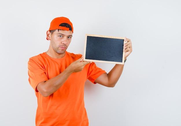 Jovem segurando uma lousa em uma camiseta laranja e boné e parecendo sensato