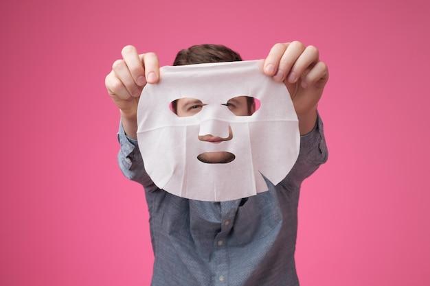 Jovem segurando uma máscara cosmética perto da câmera