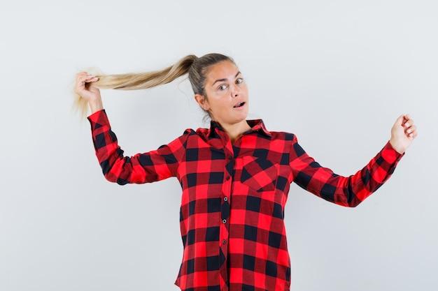 Jovem segurando uma mecha de cabelo em uma camisa quadriculada e parecendo elegante