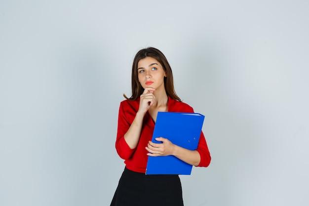 Jovem segurando uma pasta enquanto está pensando em pose de blusa vermelha
